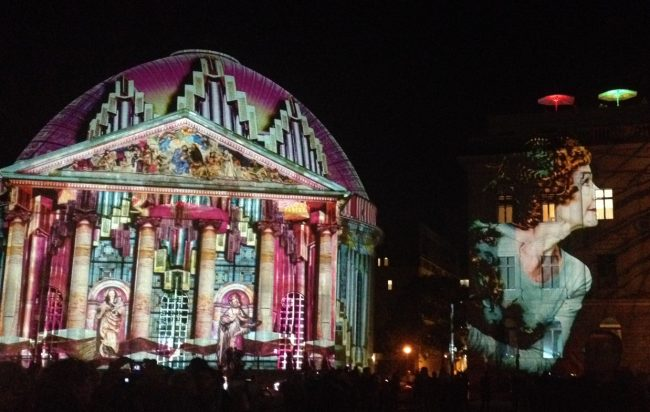 Colourful light display on St. Hedwigs Cathedral and the Hotel de Rome, Berlin